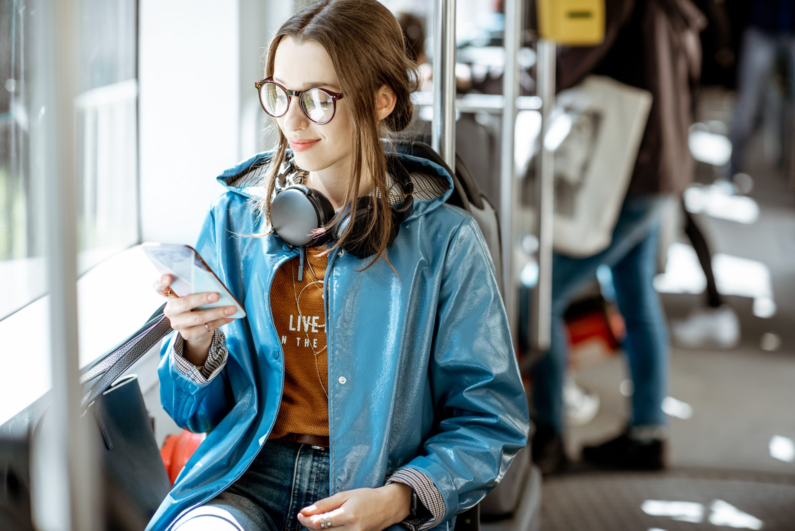 Young stylish woman using public transport, sitting with phone and headphones in the modern tram
